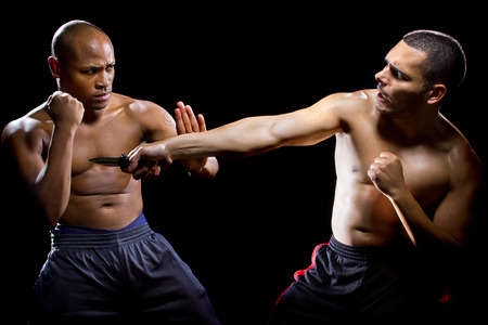 disarm: Martial arts instructor demonstrating self defense against a knife attack
