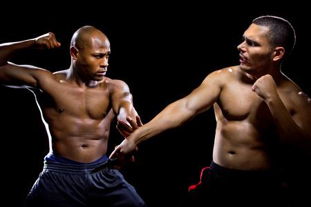 self defense: Martial arts instructor demonstrating self defense against a knife attack