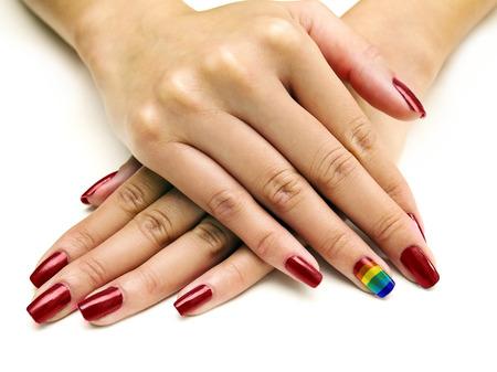 Symbolic LGBTQ pride rainbow nail art manicure on females holding hands Stok Fotoğraf