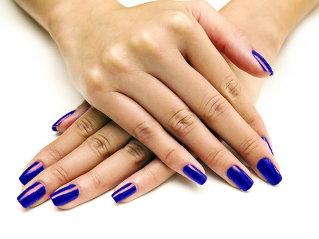 nails: Close up of female hands showing colorful nail polish on white background