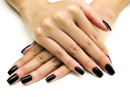 Close up of female hands showing colorful nail polish on white background