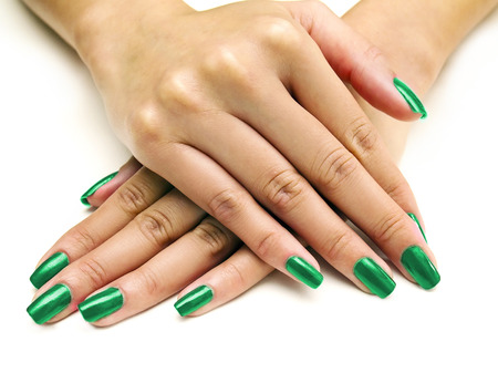 manicure: Close up of female hands showing colorful nail polish on white background