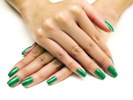 manicura: Primer plano de las manos femeninas que muestran colorido esmalte de uñas sobre fondo blanco