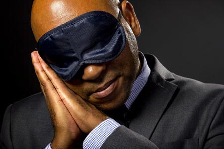 eye mask: Sleepy businessman wearing an eye mask because of jet lag