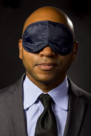 Sleepy businessman wearing an eye mask because of jet lag