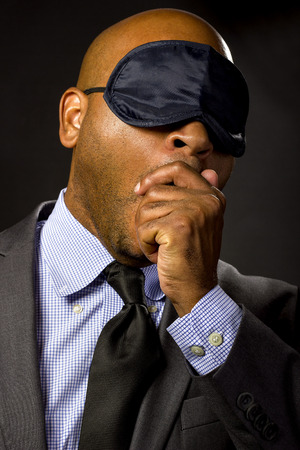 insomniac: Sleepy businessman wearing an eye mask because of jet lag