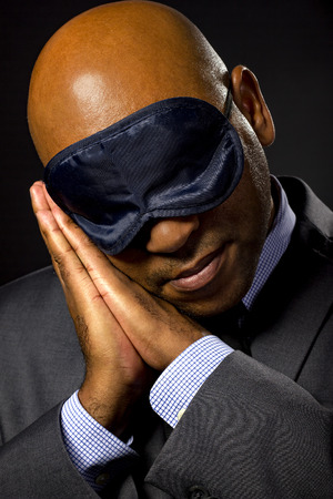 unmotivated: Sleepy businessman wearing an eye mask because of jet lag