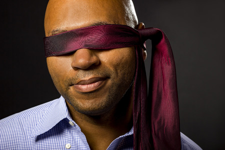 sightless: Black businessman blindfolded to represent corporate uncertainty Stock Photo
