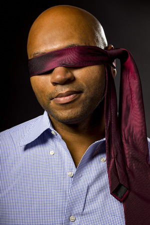 incapacity: Black businessman blindfolded to represent corporate uncertainty Stock Photo