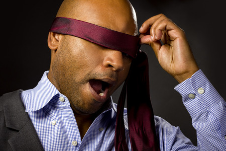 uncertainty: Black businessman blindfolded to represent corporate uncertainty Stock Photo