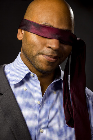 represent: Black businessman blindfolded to represent corporate uncertainty Stock Photo