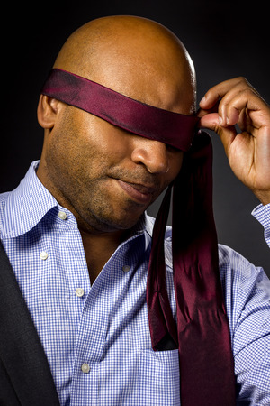 blindfolded: Black businessman blindfolded to represent corporate uncertainty Stock Photo