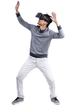 Male immersed in interactive virtual reality video game doing gestures on white background 写真素材