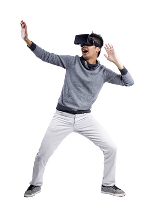 Male immersed in interactive virtual reality video game doing gestures on white background Archivio Fotografico