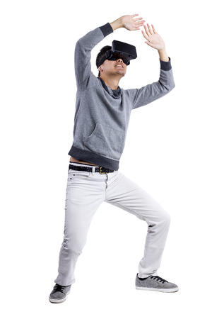 virtual reality simulator: Male immersed in interactive virtual reality video game doing gestures on white background Stock Photo