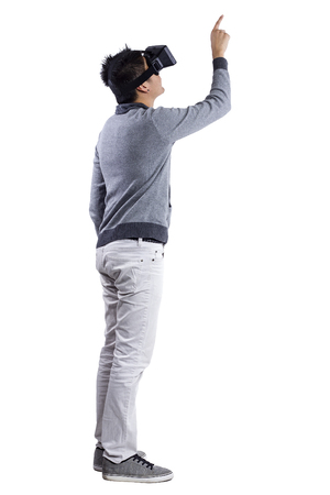 VIRTUAL REALITY: Male immersed in interactive virtual reality video game doing gestures on white background Stock Photo