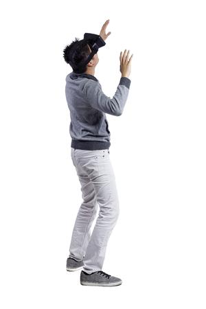 Man ondergedompeld in interactieve virtuele realiteit video game doen gebaren op een witte achtergrond