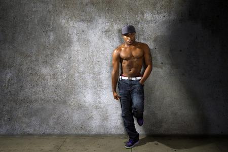 topless: Musculaires jean de mod�lisation de l'homme noir et le torse torse nu sur le mur de b�ton urbain
