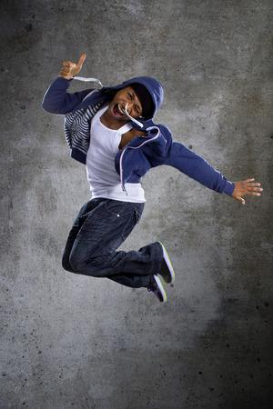 breakdancer: Black urban break dancer wearing a blue hoodie and jumping Stock Photo