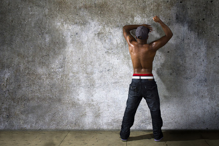 topless jeans: Muscular black man modeling jeans and shirtless torso on urban concrete wall