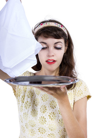 unveiling: Retro style female waitress unveiling a surprise hidden in a tray and napkin