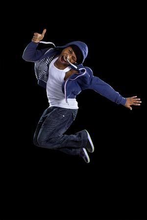 hop: Black urban break dancer wearing a blue hoodie and jumping Stock Photo