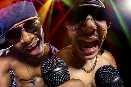 raperos: Rappers having a hip hop music concert with microphones Foto de archivo
