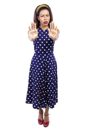 fedup: Woman in polka dot blue dress looks irritated and holding hands in a stop gesture