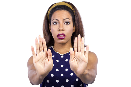 Woman in polka dot blue dress looks irritated and holding hands in a stop gesture