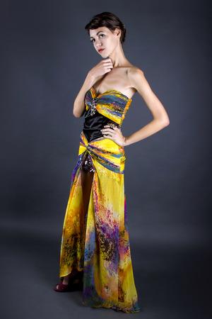 silk tie: Woman wearing a yellow silk tie dye dress on a dark studio background Stock Photo