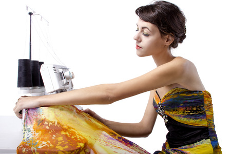 designer at work: Woman wearing a yellow dress and stitching with a sewing machine