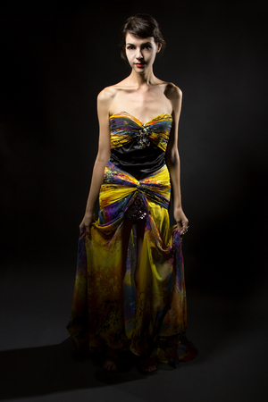 Woman modeling a yellow dress on a dark background for contrast Stock Photo