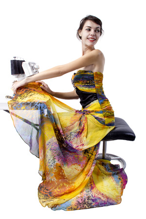 stitching machine: Woman wearing a yellow dress and stitching with a sewing machine