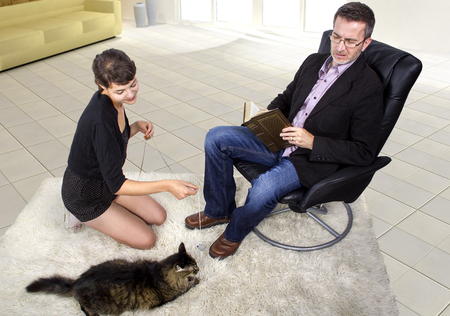 adopted: Family playing with a newly adopted pet cat at home Stock Photo