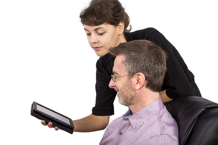 single father: Young female giving her single father a tablet as a gift Stock Photo