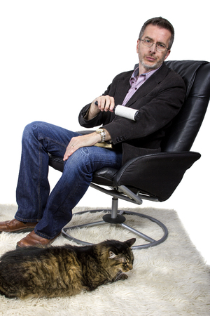 lint: Man using a lint roller to clean off cat fur from his jacket Stock Photo