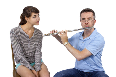 teaching music: Music instructor teaching female student how to play the flute