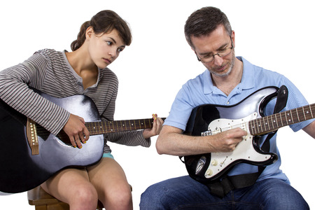 teaching music: Female looking frustrated with male music instructor teaching how to play guitar Stock Photo