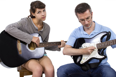 apathetic: Female looking frustrated with male music instructor teaching how to play guitar Stock Photo