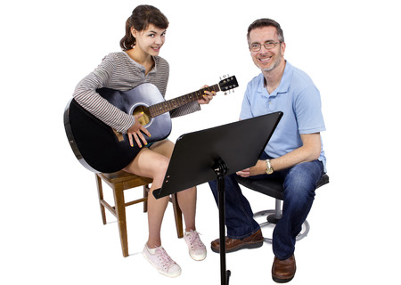 how to: Music teacher tutoring young female student how to play guitar