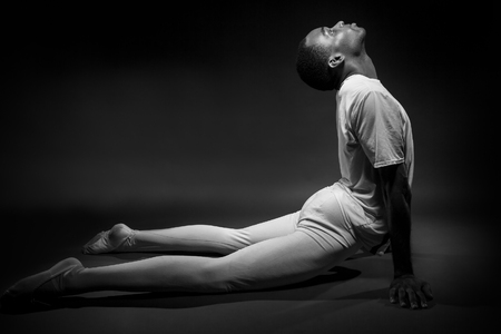 contortionist: Classical ballet dancer warming up with stretches in black and white