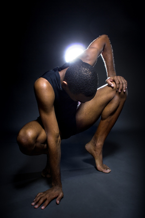 warm up: Black male dancer practicing warm up exercises for flexibility