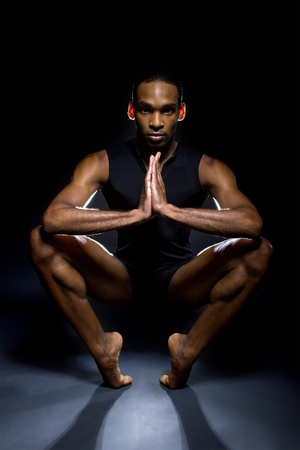Black male dancer practicing warm up exercises for flexibility