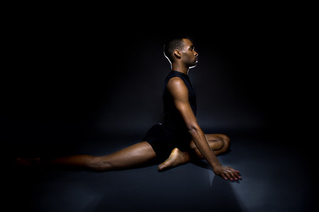 flexibility: Black male dancer practicing warm up exercises for flexibility