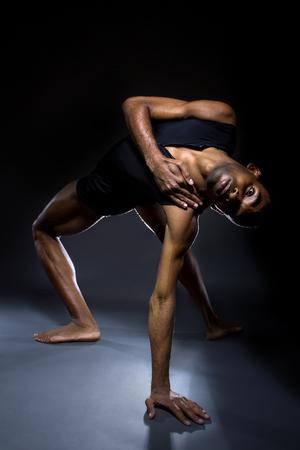ballet hombres: Bailarín negro practicando ejercicios de calentamiento para la flexibilidad