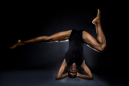 contortionist: Black male dancer practicing warm up exercises for flexibility