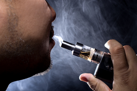 controversial: Man with concealed identity smoking a controversial vape is a health risk