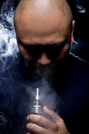 concealed: Man with concealed identity smoking a controversial vape is a health risk