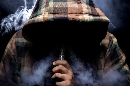 hombre fumando: Hombre con identidad oculta fumando un vape controvertido es un riesgo para la salud