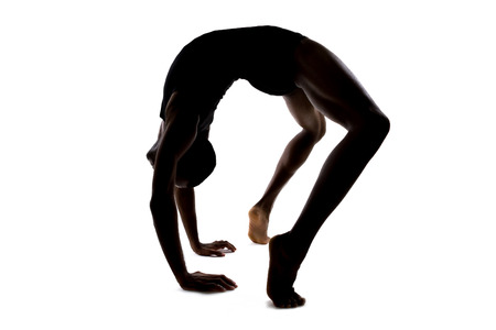contortion: Silhouette of a flexible male dancer posing and balancing on white background